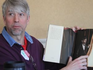 Image of man with book at Voices training session