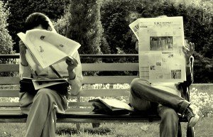 Image of two people reading the newspaper