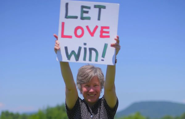 Image of woman holding Let Love Win sign