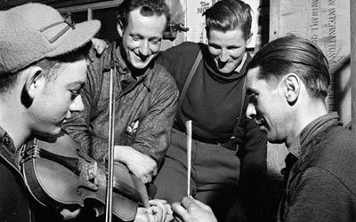 Image of men playing fiddles in a circle
