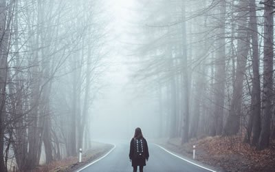 Image of woman on road under trees