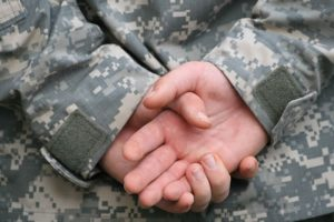 Image of veterans' hands clasped behind back