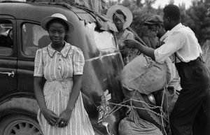 Image of migrant workers beside car