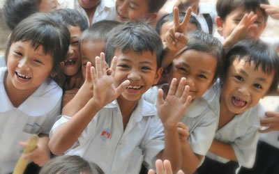 Image of children smiling and waving