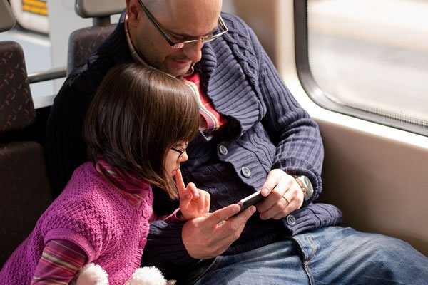 Image of father and daughter looking at smartphone