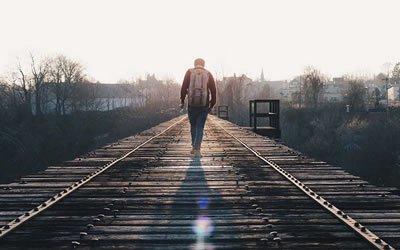 Image of man walking along railroad tracks
