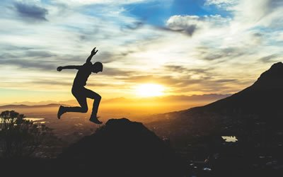 Image of person jumping in mountains