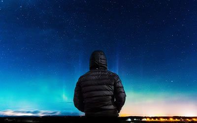 Image of person in parka beneath the night sky