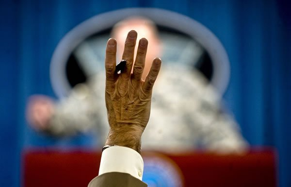 Image of hand raised at press conference