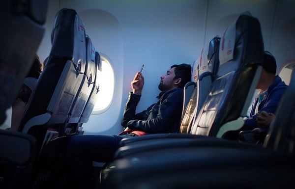 Image of man with phone on plane
