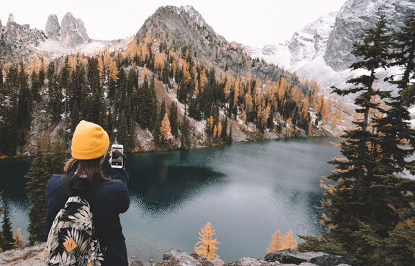 Image of woman with phone on mountaintop