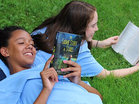 Image of two girls reading on the grass.