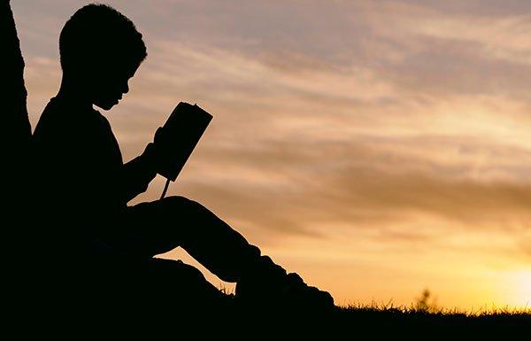 Image of boy reading against sunset