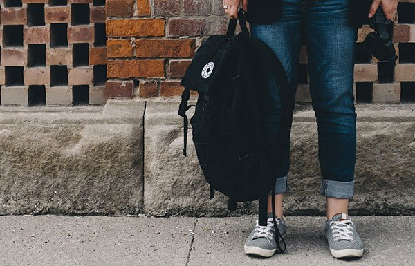 Image of teenager's feet and backpack