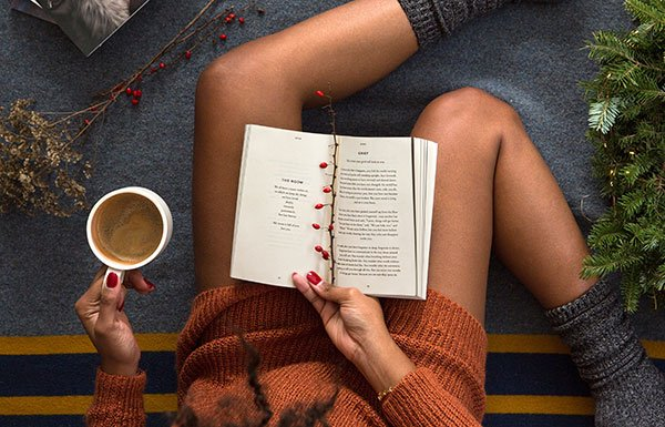 Image of young woman reading a book with coffee