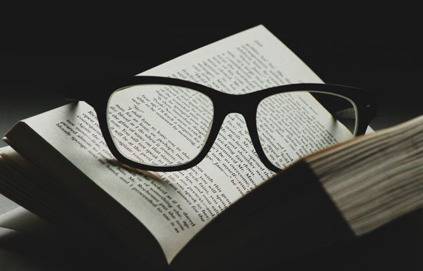 Image of reading glasses on open book