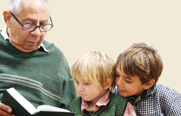 Image of older man reading book with two boys