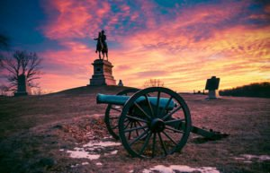 Image of cannon and statue at sunset