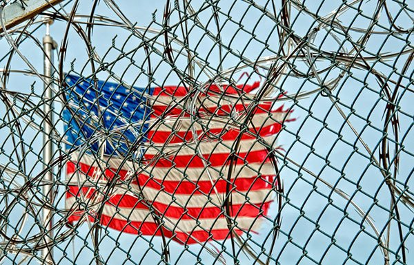 Image of flag behind chain link fence