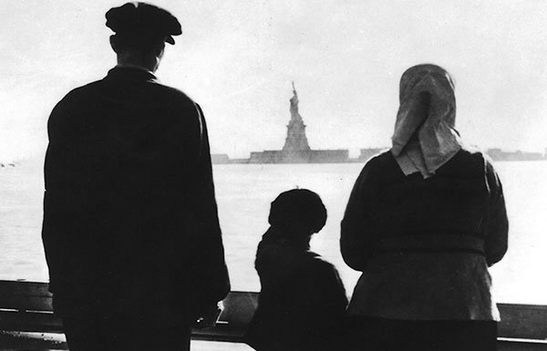 Image of immigrant family looking at Statue of Liberty