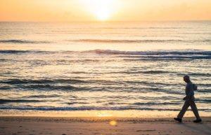 Image of man walking along a beach at sunset