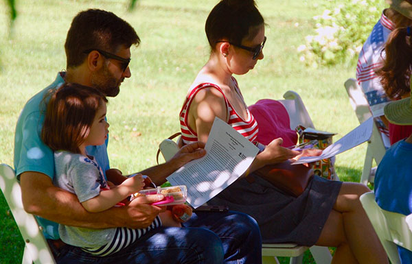 Parents reading with a child under a tree