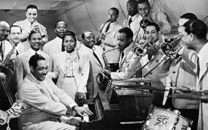 Duke Ellington and other musicians around a piano