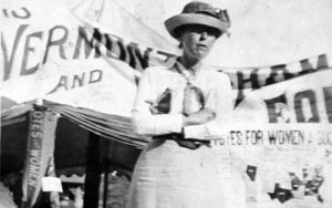 Suffragette standing before a banner