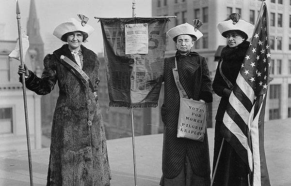 Suffragists by sign with flag