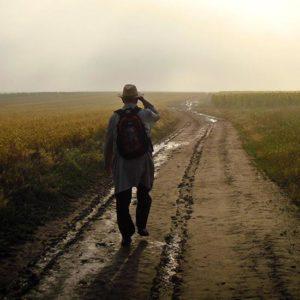 Man walking on dirt road toward horizon