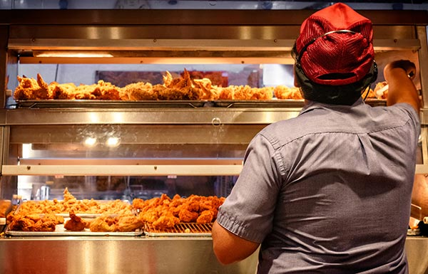 Fast food worker with fried chicken on shelves