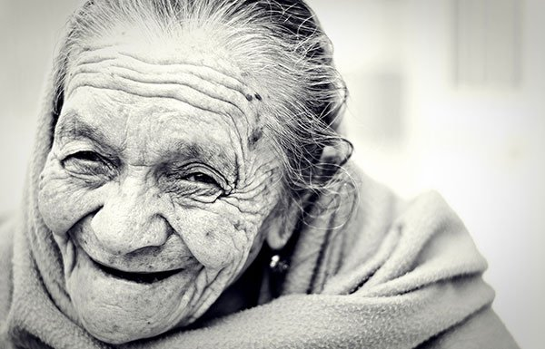Old woman laughing while wearing a shawl