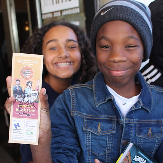 Boy holding a Vermont Reads bookmark while girl smiles behind him