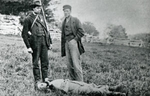Two soldiers standing by dead Fenian