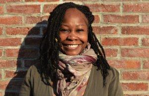 Poet Shanta Lee Gander standing against a brick wall