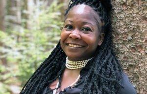 Poet Shanta Lee Gander leaning against a tree