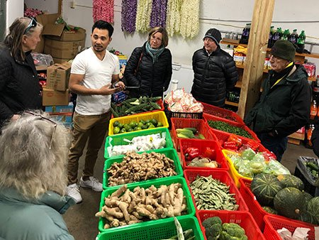 Man at market shows vegetables to others