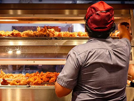 Fast food worker with shelf of fried chicken
