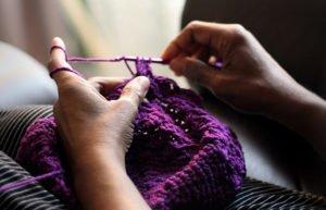 Hands knitting with purple yarn