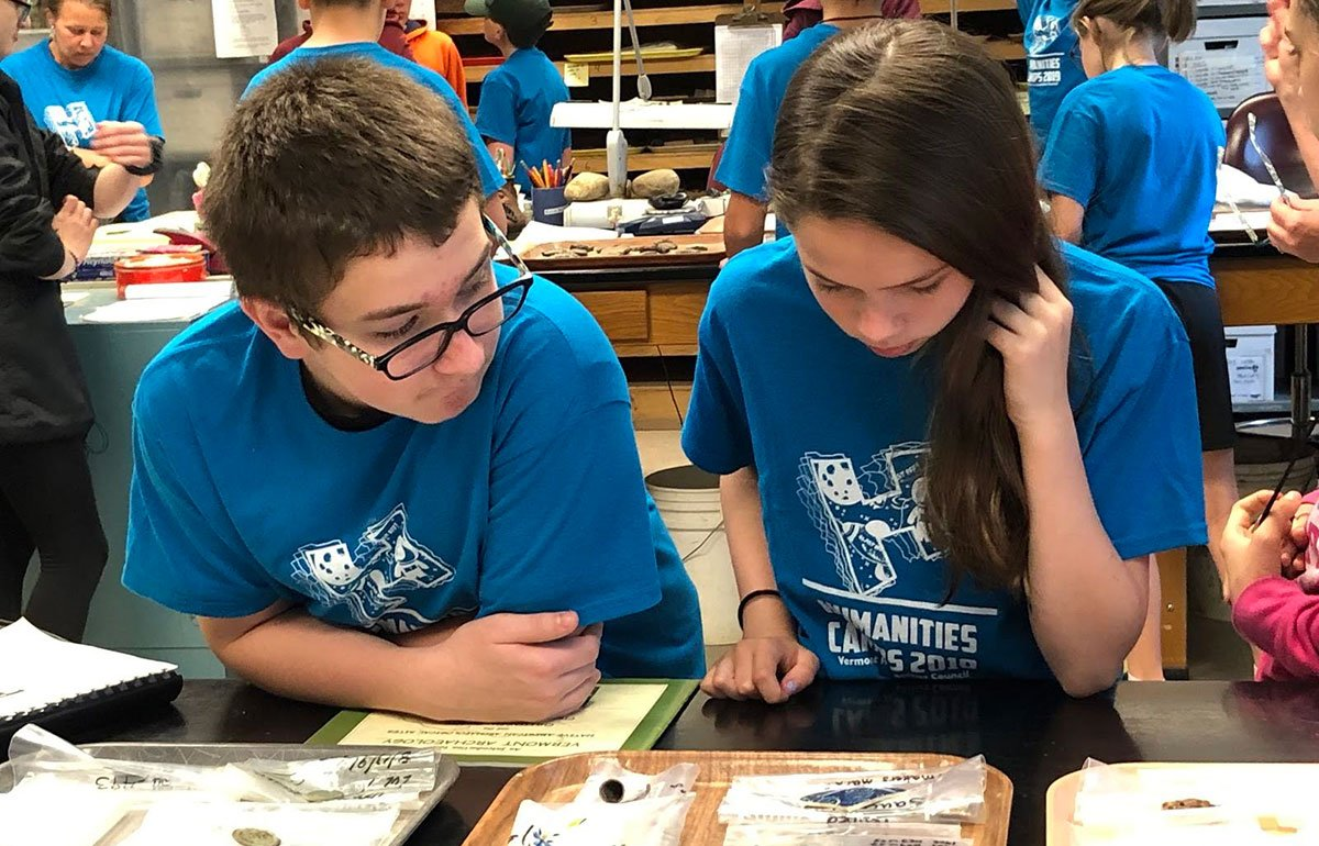 Humanities Campers looking at objects on table in museum