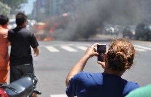 Woman taking photo of burning car