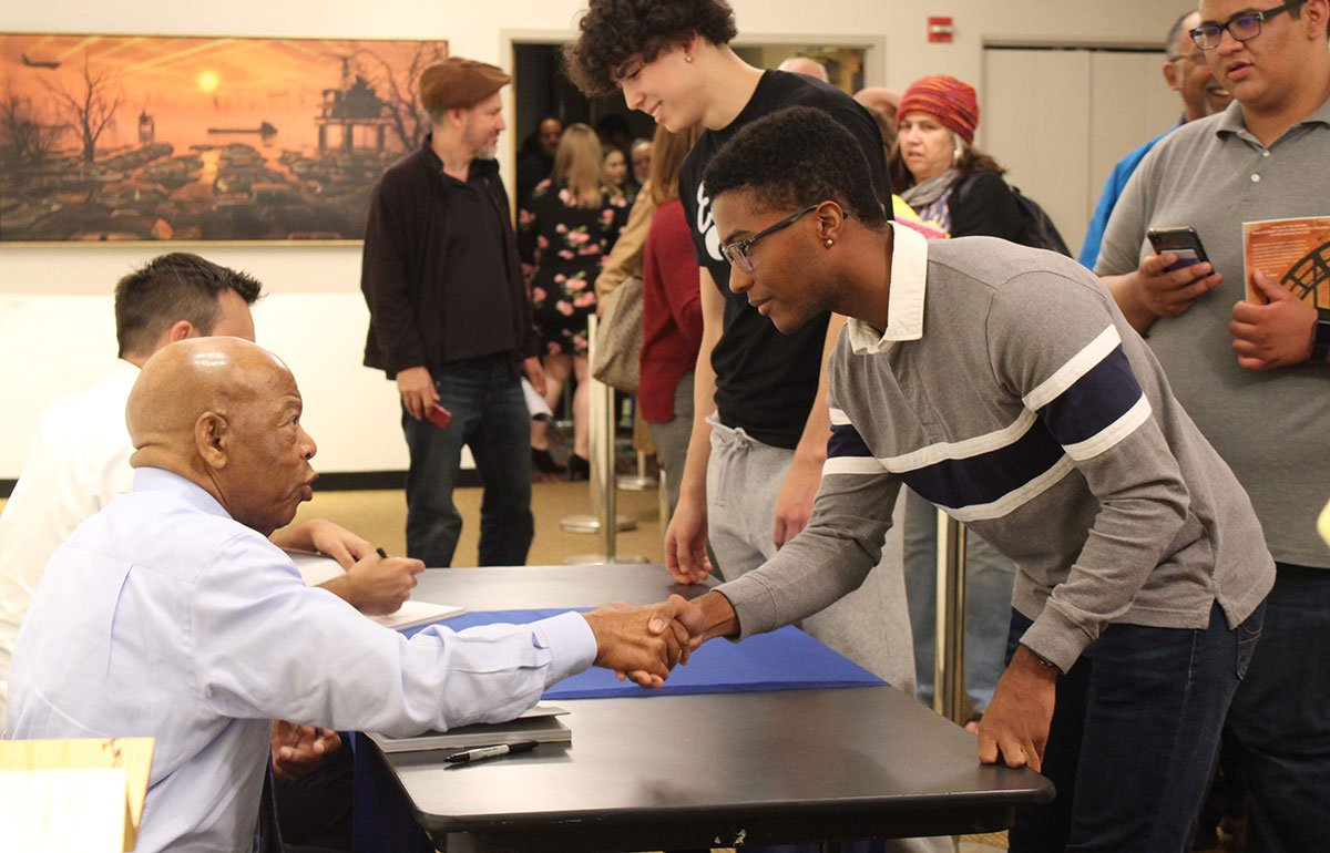 John Lewis shaking hands with young fan