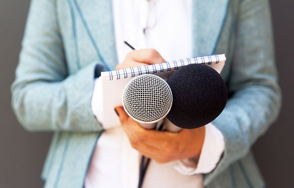 Reporter holding a microphone and notebook