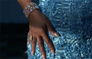 Woman's hand with diamonds on blue dress