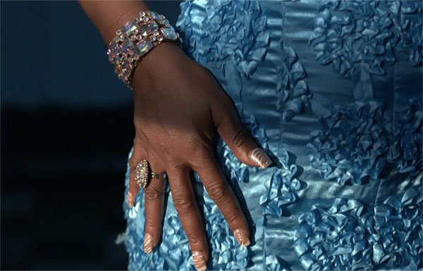 Woman's hand with diamonds on blue dress