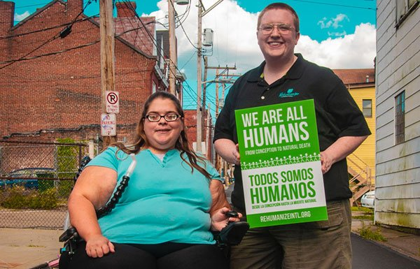 """Woman in wheelchair and standing women holding """"We Are All Humans"""" sign"""