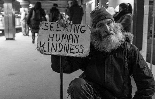 "Man on subway platform holding ""seeking human kindness"" sign"