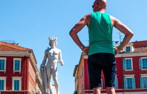 Man with hands on hips looking at statue