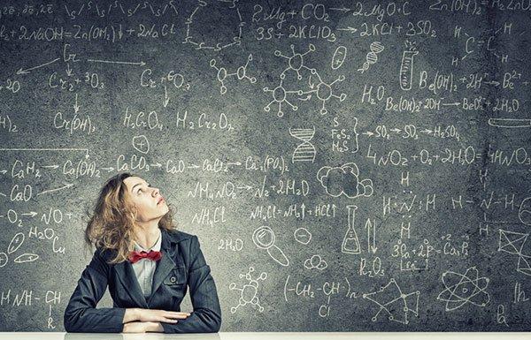 Nerdy woman looking up at blackboard