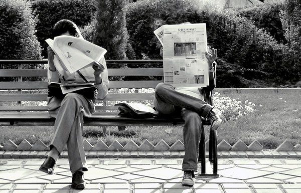 Two people reading different newspapers on a park bench